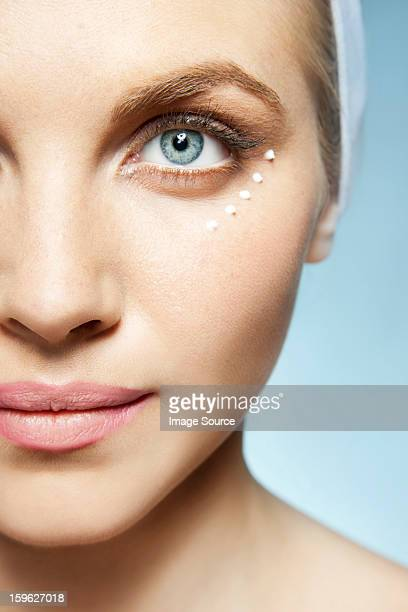 Woman with eye cream around eye