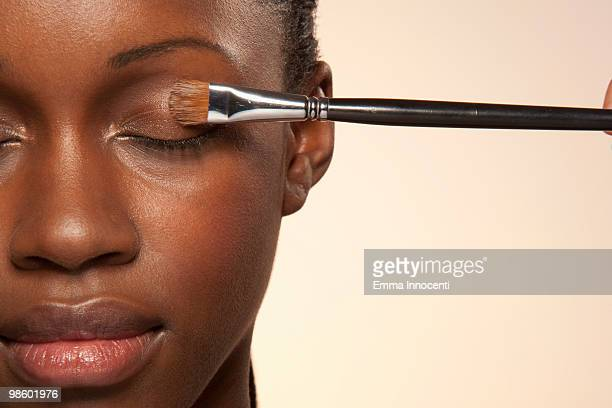 woman with eye make up brush on eye - make up stockfoto's en -beelden