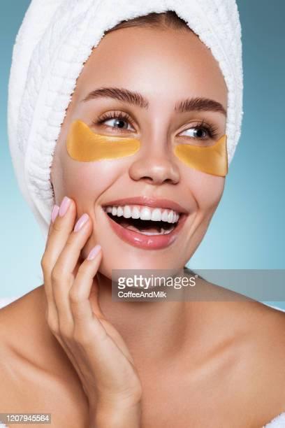 顔のマッサグを持つ目のパッチを持つ女性 - つぎあて ストックフォトと画像