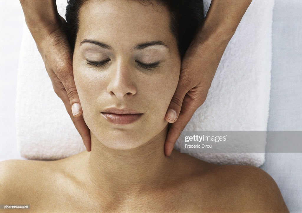 Woman with eyes closed and bare shoulders receiving neck massage : Stockfoto