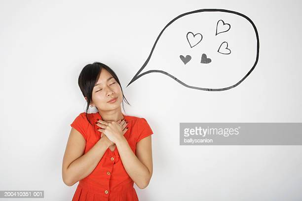 Woman with eyes closed and hands to chest with hearts in bubble