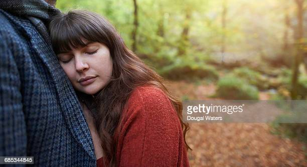 Woman with eyes closed and man in Autumn woodland.