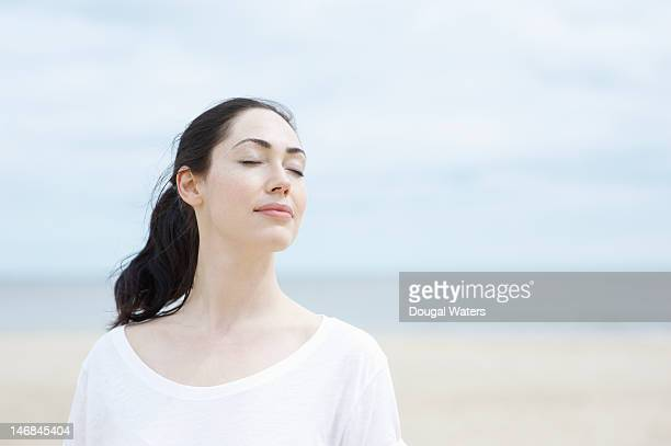 Woman with eyes closed at beach.