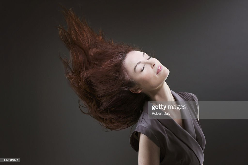Woman with eyes closed flipping hair : Stock Photo