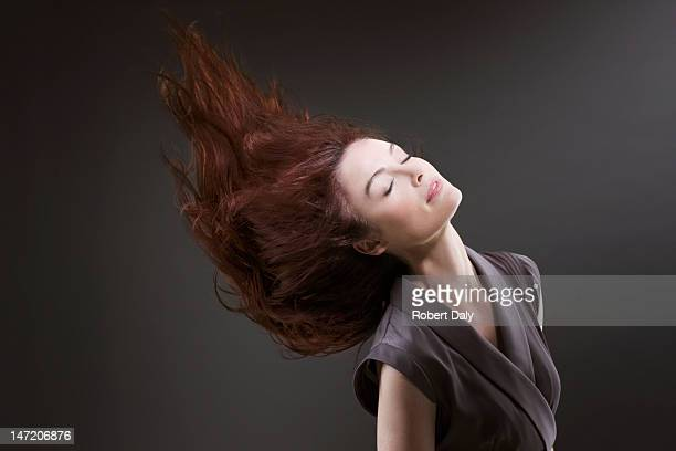 Woman with eyes closed flipping hair