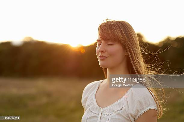 Woman with eyes closed in front of sunset.