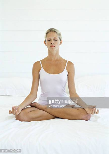 Woman with eyes closed in lotus position, full length, white background