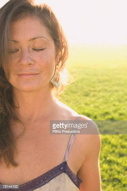 Woman with eyes closed in sunlit meadow