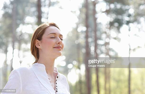 woman with eyes closed in woodland. - tranquility stock pictures, royalty-free photos & images
