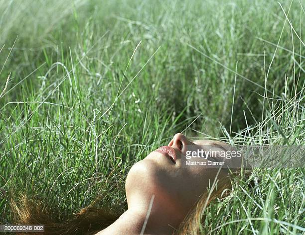 Woman with eyes closed lying in grass, close up
