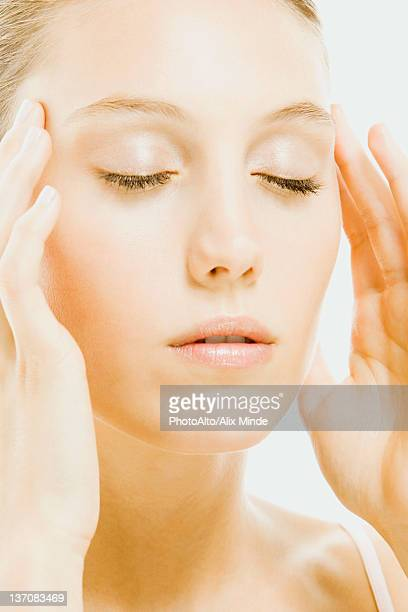 Woman with eyes closed massaging temples