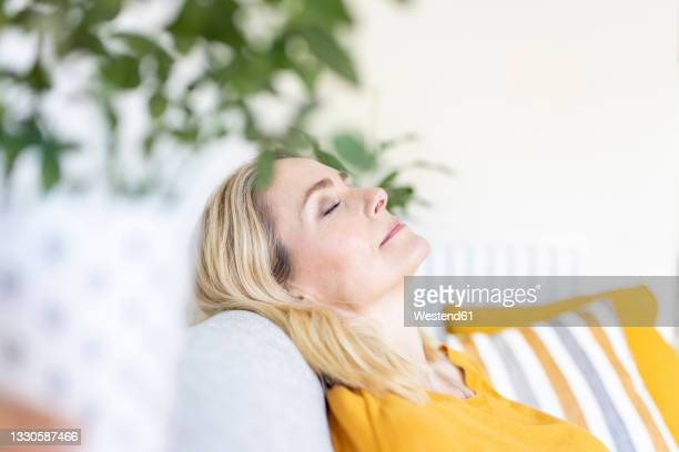 woman with eyes closed relaxing at home - sofa stock pictures, royalty-free photos & images