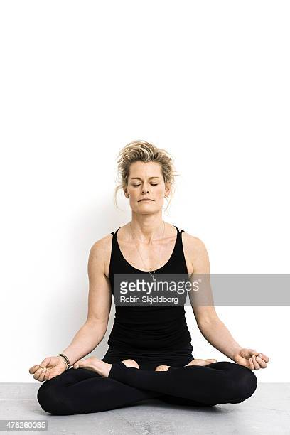 Woman with eyes closed sitting in lotus position