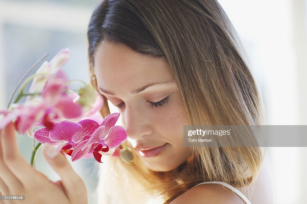 Woman with eyes closed smelling orchid : Stock Photo
