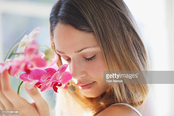 Woman with eyes closed smelling orchid