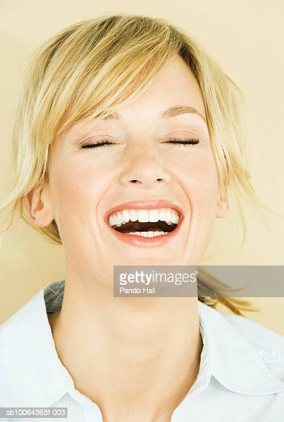 woman with eyes closed, smiling, close-up - one mid adult woman only stock pictures, royalty-free photos & images