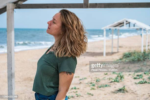 woman with eyes closed standing at beach - capelli mossi foto e immagini stock