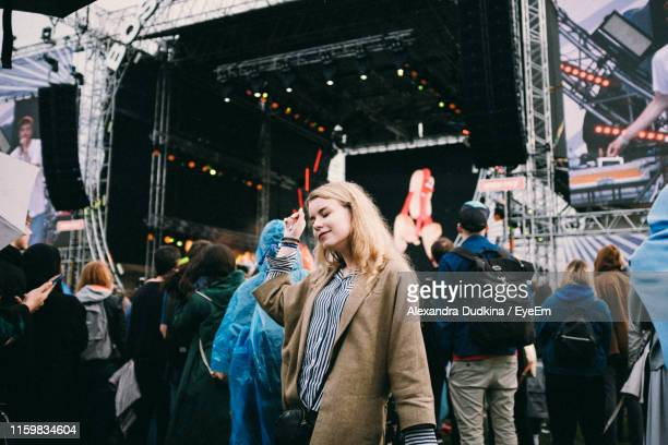 woman with eyes closed standing at music concert - music festival stock-fotos und bilder