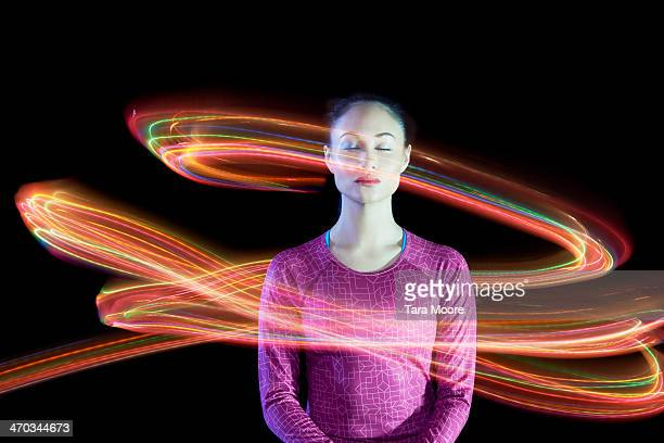 woman with eyes closed surrounded by light trails - umgeben stock-fotos und bilder