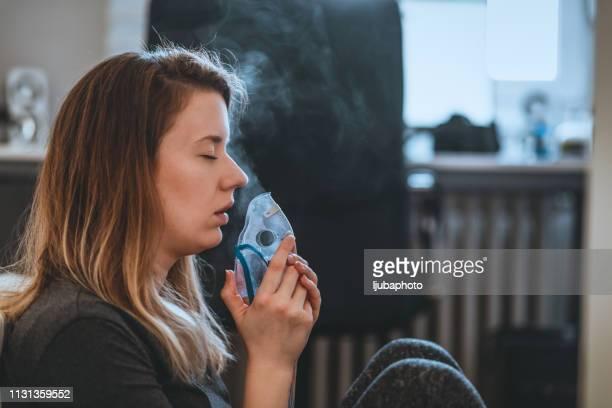 woman with eyes closed using the inhalation mask - amigdalite imagens e fotografias de stock