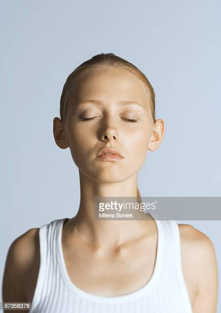 Woman with eyes closed wearing tank top, portrait