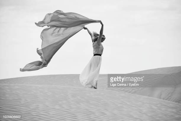 woman with fabric standing on sand at beach against sky - liga cerina stock pictures, royalty-free photos & images