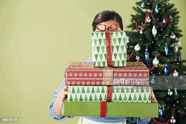 Woman with face covered by stack of presents