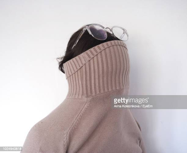 woman with face covered by turtleneck t-shirt against white background - col roulé photos et images de collection