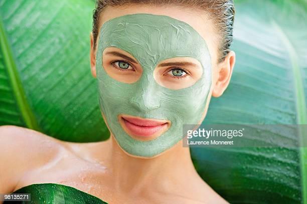 woman with face green mud mask among big leaves - lichaamsverzorging en schoonheid stockfoto's en -beelden