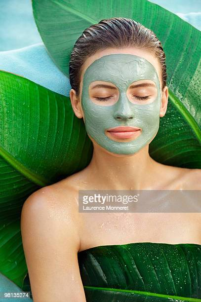 Woman with face green mud mask on big leaves