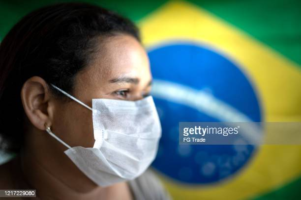 woman with face mask and brazilian flag on background - brasile foto e immagini stock