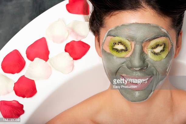 Woman with face mask and kiwi in bath