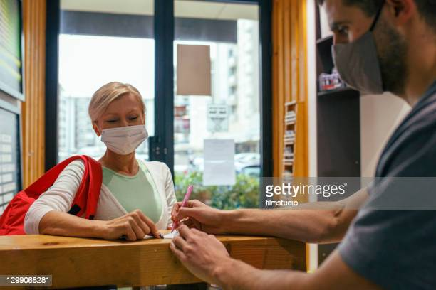woman with face mask checking at gym - leisure facilities stock pictures, royalty-free photos & images