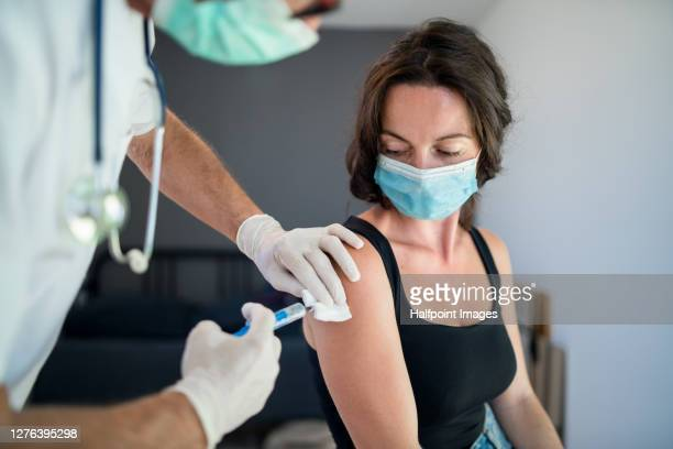 woman with face mask getting vaccinated, coronavirus concept. - syringe stock pictures, royalty-free photos & images