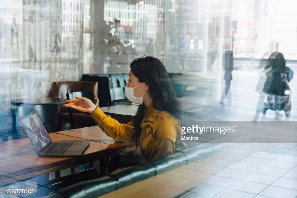 woman with face mask having video call using laptop - video conference stock pictures, royalty-free photos & images