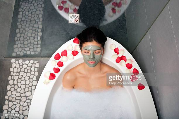 Woman with face mask in bubble bath