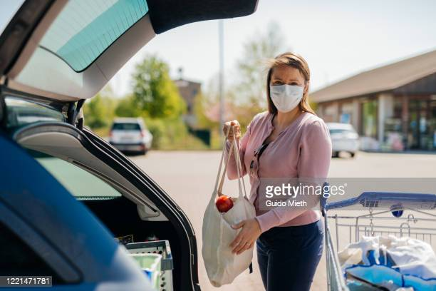 woman with face mask loading a car. - guido mieth stock pictures, royalty-free photos & images