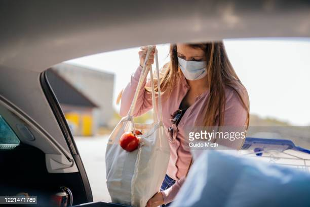 woman with face mask loading car after shopping while covid-19. - guido mieth stock pictures, royalty-free photos & images