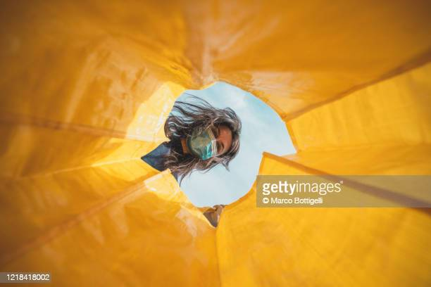 woman with face mask looking through an empty shopping bag - binnenin stockfoto's en -beelden