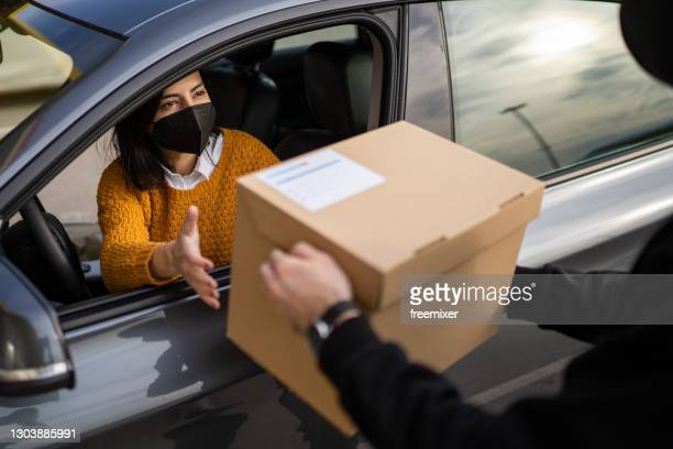 woman with face mask picking order from her car at a curbside pickup - curbside pickup stock pictures, royalty-free photos & images