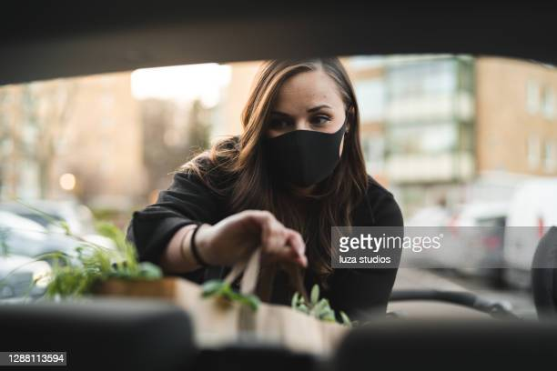 woman with face mask putting grocery bags in the car - sweden stock pictures, royalty-free photos & images
