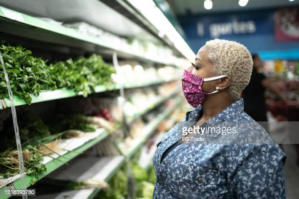 woman with face mask shopping at supermarket - face mask stock pictures, royalty-free photos & images