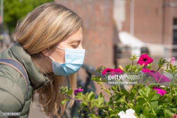 woman with face mask smelling flowers - 嗅ぐ ストックフォトと画像