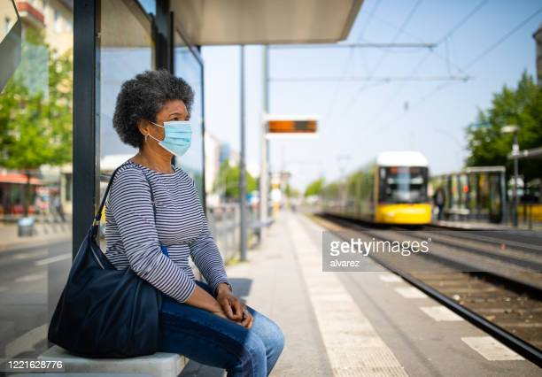 woman with face mask travelling in berlin tram during covid-19 outbreak - railroad station stock pictures, royalty-free photos & images