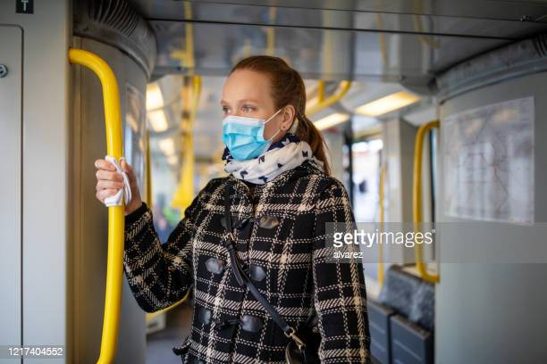 woman with face mask travelling in metro during covid-19 outbreak - arrival stock pictures, royalty-free photos & images