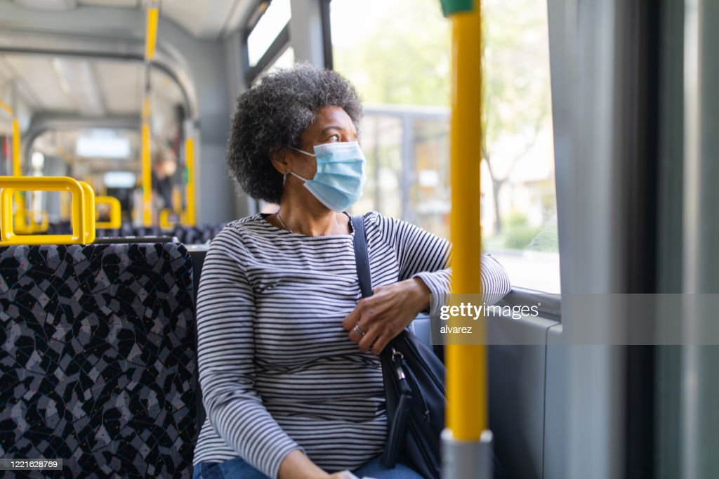 Woman with face mask travelling in the tram during Covid-19 outbreak : Stock Photo