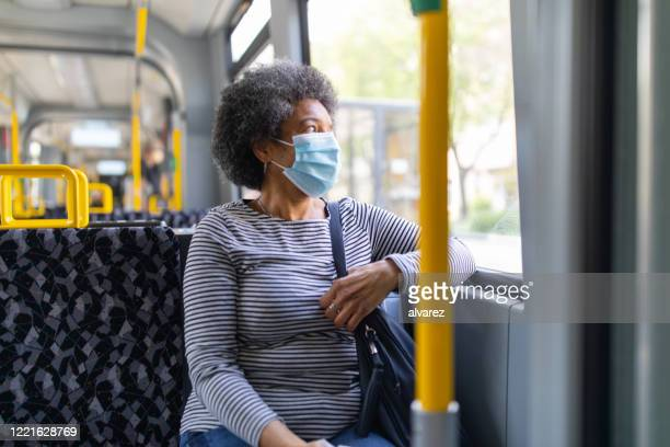 woman with face mask travelling in the tram during covid-19 outbreak - transporte público imagens e fotografias de stock