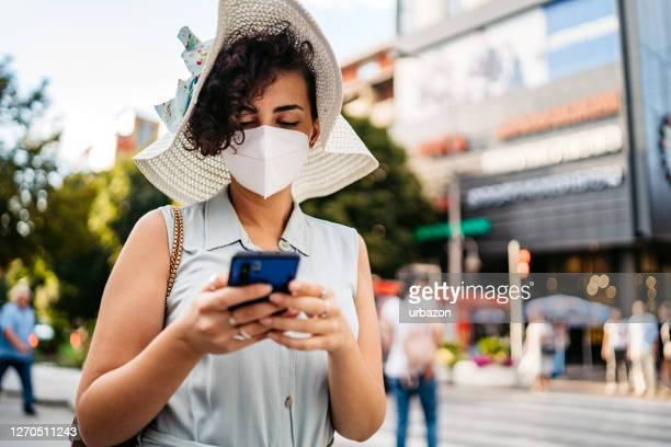 woman with face mask using phone downtown - phone message stock pictures, royalty-free photos & images
