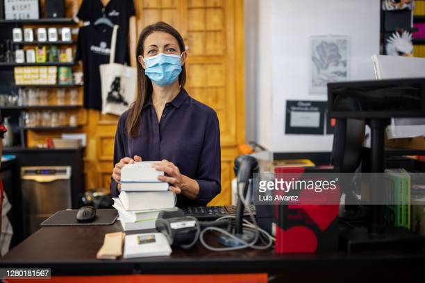 woman with face mask working at bookstore checkout - assistant stock pictures, royalty-free photos & images