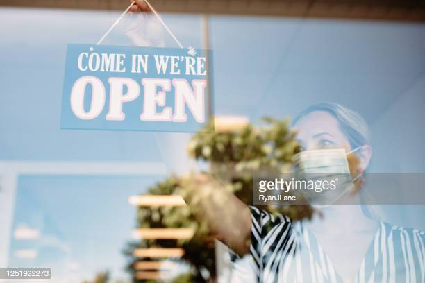 woman with face masks hangs up a business open sign - reopening stock pictures, royalty-free photos & images